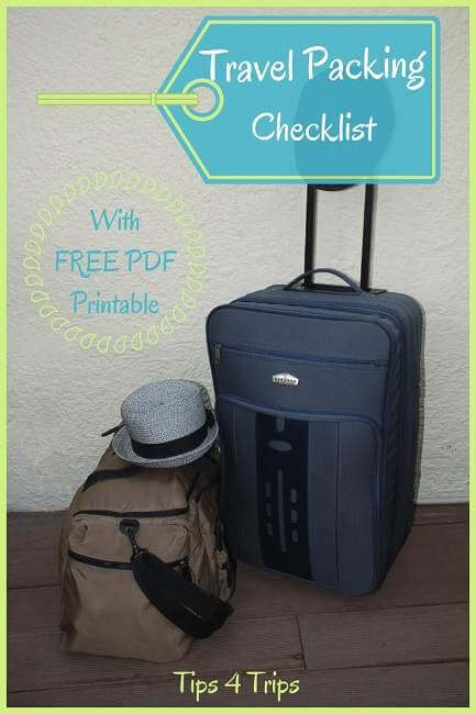 Hats hanging on blue suitcase and duffel bag packed with a trip free printable packing list